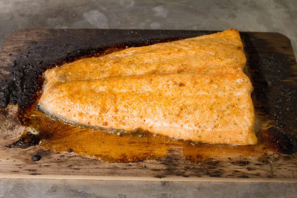 Finished fish on a slightly blackened plank