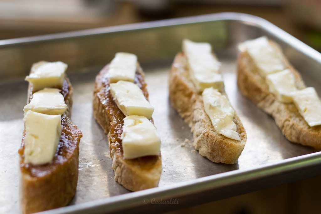 Brie, with the crust off, on the open-face sandwiches ready to go in the oven.